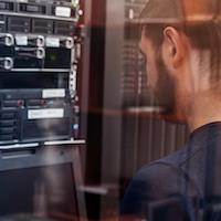 Ein junger Mann steht vor einer Serverwand.