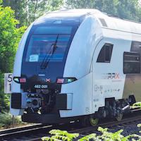 Ansicht eines RRX-Regionalzuges während der Fahrt durch einen Waldabschnitt.