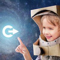 Kleiner Junge in einem aus Pappe gebastelten Astronautenkostüm weist mit einem Fingerzeig auf das nextTicket-Logo (C mit Pfeil in der Mitte).