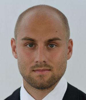 Portraitfoto Dr. Dominik Elsmann: Mann mit Glatze im Anzug